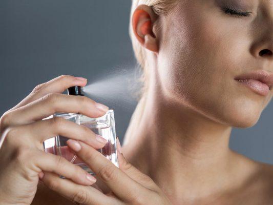 Žena nanosi parfem na vrat
