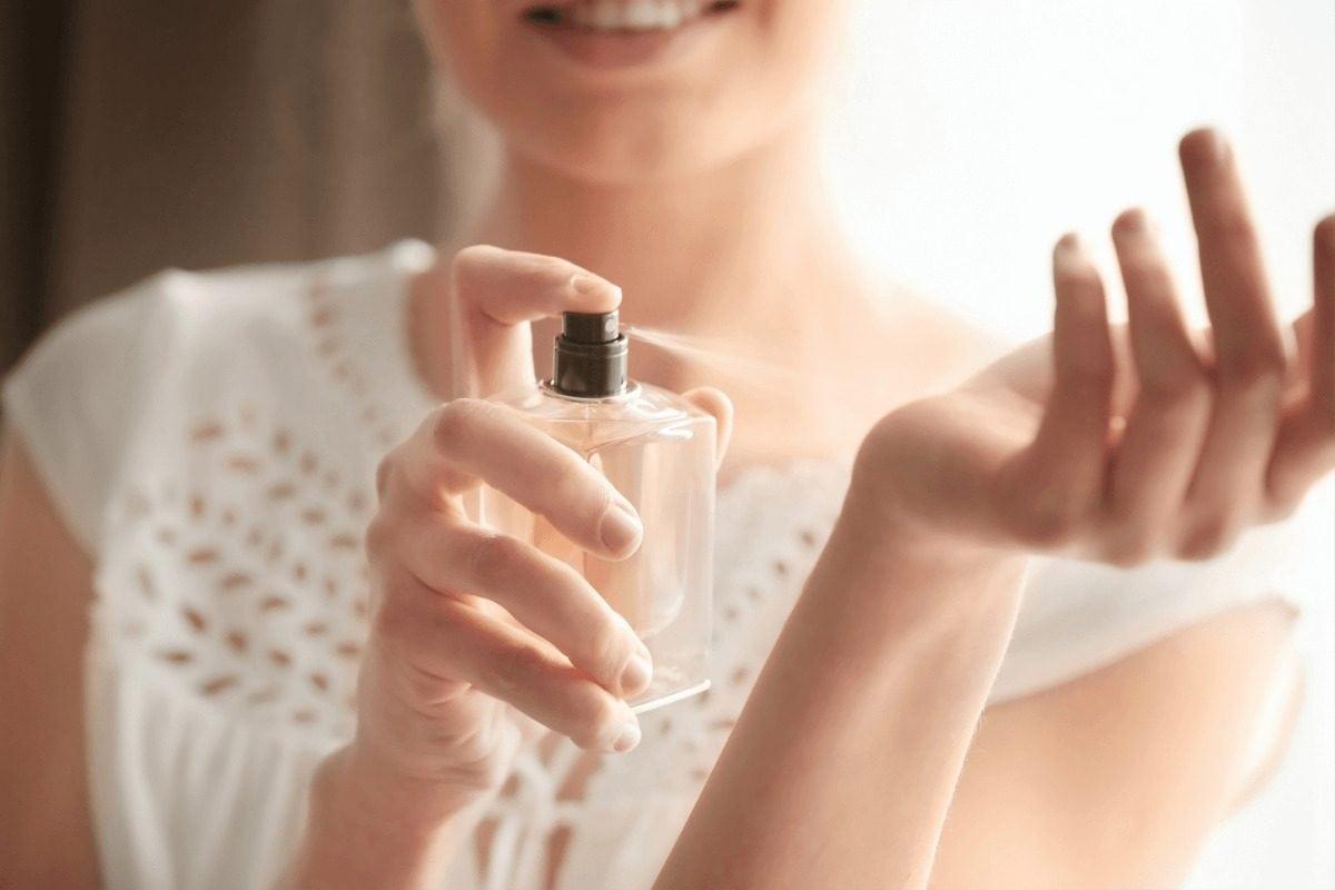 Lepa mlada devojka nanosi parfem na svoju ruku